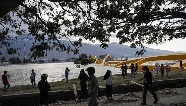 La gente inspecciona el puente 'Palu Empat' (R) que fue destruido durante un tsunami en la playa Talise en Palu, Sulawesi Central, Indonesia. (Foto: EFE)