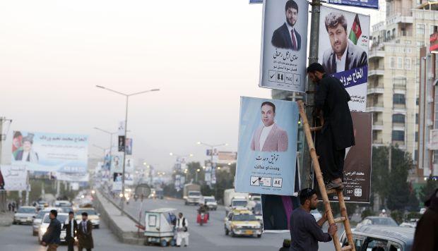 Hombres afganos instalan un póster de la campaña de un candidato para las próximas elecciones parlamentarias en el centro de Kabul, Afganistán. (Foto: EFE)
