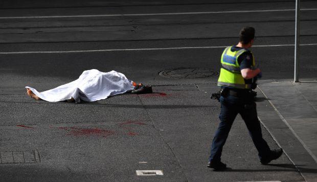 El cadáver de una víctima yace sobre el asfalto después de que un hombre armado con un cuchillo atacase a varias personas en la calle Bourke de Melbourne (Foto: EFE)