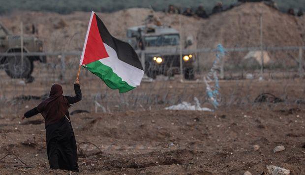 Una mujer palestina ondea una bandera durante enfrentamientos con soldados israelíes en la Franja de Gaza. (Foto: EFE)