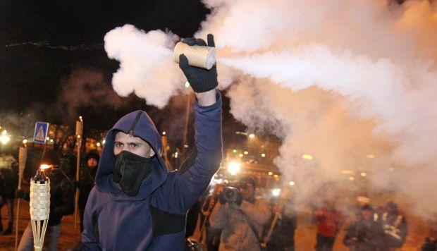 Activistas ucranianos sostienen antorchas y gritan consignas durante una concentración para conmemorar el quinto aniversario de la revolución del