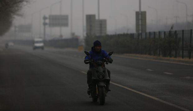 Un hombre chino monta su bicicleta eléctrica durante un día contaminado en Pekín, China. (Foto referencial: EFE)