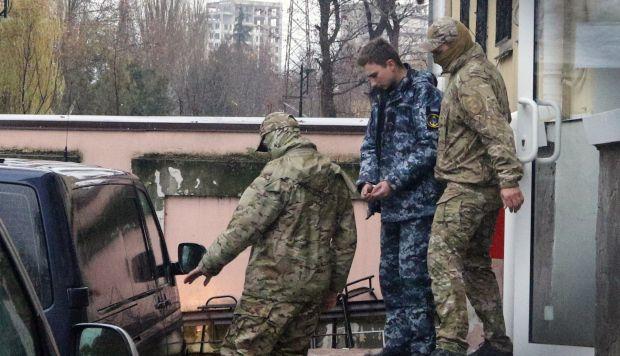 Miembros de los Servicios de Seguridad de Rusia y escoltan a un marinero ucraniano detenido desde el tribunal de Simferópol, en Crimea. (Foto: EFE)