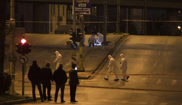 Expertos forenses griegos buscan en la escena después de que una poderosa bomba explotara fuera de la estación de televisión griega privada, en Faliro, Atenas. (Foto: AP)