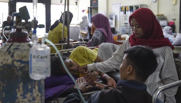 Miembros de la familia visitan a un sobreviviente del tsunami en una sala de hospital en Kalianda, provincia de Lampung. (Foto: AFP)
