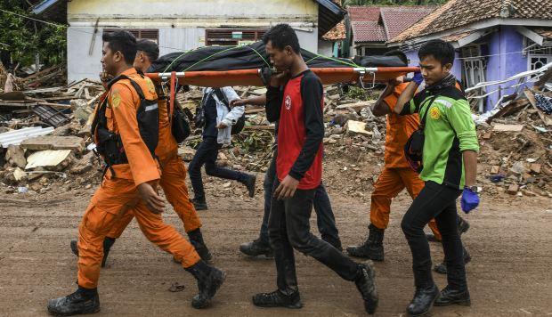 Miembros de un equipo indonesio de búsqueda y rescate llevan el cuerpo de una víctima recuperada de una casa colapsada en una bolsa de cadáveres en Rajabasa, en la provincia de Lampung. (Foto: AFP)