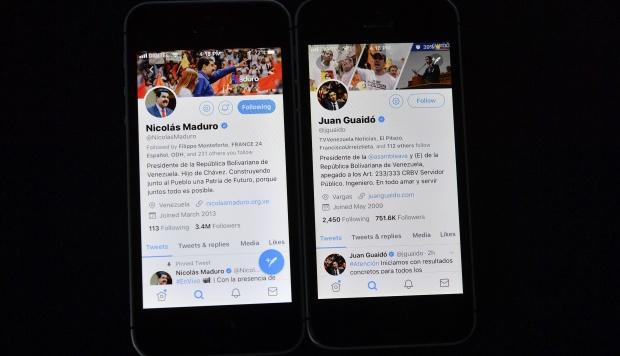 Un hombre muestra los perfiles de redes sociales del presidente venezolano Nicolás Maduro y el jefe de la Asamblea Nacional de Venezuela, Juan Guaido, quien se declaró a sí mismo