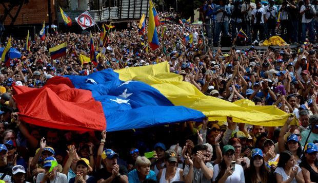 La gente escucha al jefe de la Asamblea Nacional de Venezuela, Juan Guaido, durante un mitin de oposición en masa contra el líder Nicolás Maduro, en el que se declaró a sí mismo el