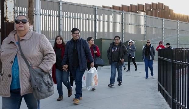 Los compradores caminan hacia el Puerto de Entrada de San Ysidro después de realizar compras en los centros comerciales a lo largo de la frontera entre los Estados Unidos y México. (Foto: AFP)