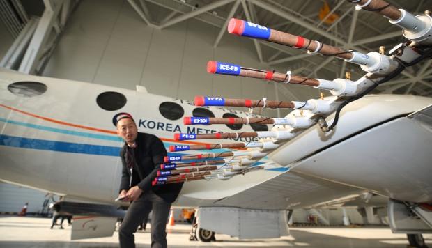 Un hombre mirando un avión de la Administración Meterológica de Corea listo para dispersar el yoduro de plata, un compuesto que se cree causa la lluvia, en una percha en el aeropuerto de Gimpo en Seúl. (Foto: AFP)