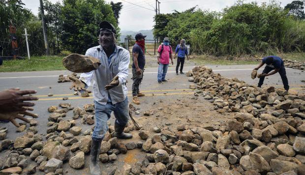 Los indígenas establecieron una barricada con piedras para bloquear la carretera Panamericana durante una protesta en La Agustina. (Foto: AFP)