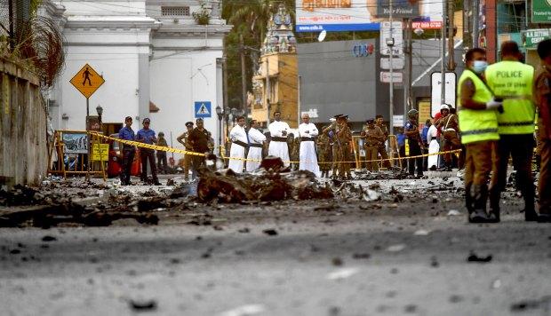 Sacerdotes de Sri Lanka miran los escombros de un automóvil después de que explota cuando la policía intentó desactivar una bomba cerca del Santuario de San Antonio en Colombo. (Foto: AFP)