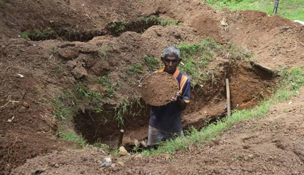 El trabajador del cementerio quita tierra mientras cava una tumba en el cementerio Madampitiya en Colombo el 23 de abril de 2019. (Foto: AFP)