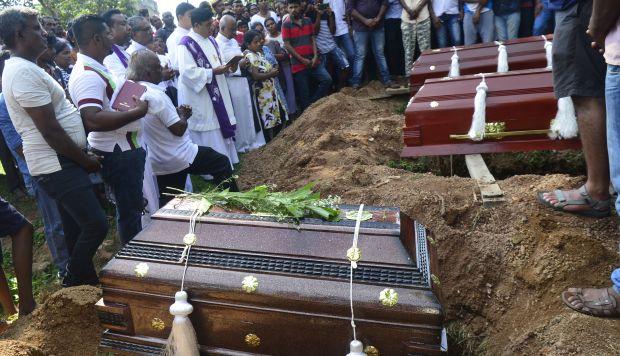 Un sacerdote administra un ritual de entierro para una víctima de explosión de bomba en un cementerio en Colombo el 23 de abril de 2019. (Foto: AFP)