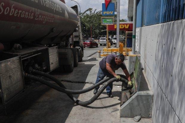 Un trabajador prepara las mangueras de un camión cisterna para llenar tanques de combustible, este viernes, en una estación de servicio de Caracas (Venezuela). (Foto: EFE)