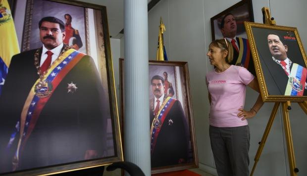 La activista de Codepink, Medea Benjamin, habla a los reporteros, rodeada de fotos del ex presidente de Venezuela Hugo Chávez y del actual presidente Nicolás Maduro. (Foto: AFP)