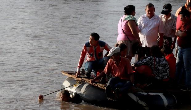 Migrantes y residentes utilizan una balsa improvisada para cruzar ilegalmente el río Suchiate, desde Tecun Uman, en Guatemala hasta Ciudad Hidalgo, estado de Chiapas, México. (Foto: AFP)