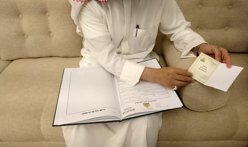 El clérigo saudita Abdelmohsen al Ajemi, muestra muestras de contratos de boda. (Foto: AFP)