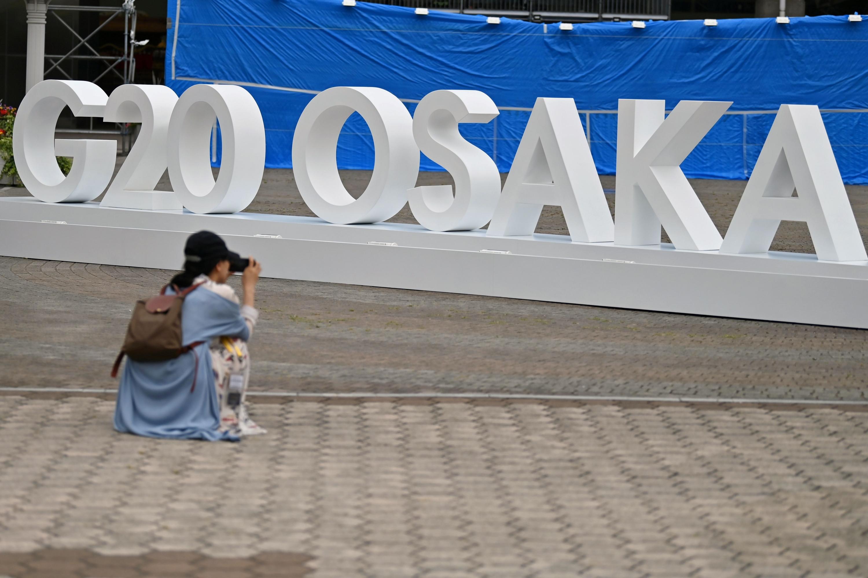 Una mujer toma una fotografía de un diseño del G20 establecido fuera de la sede de la Cumbre. (Foto: AFP)