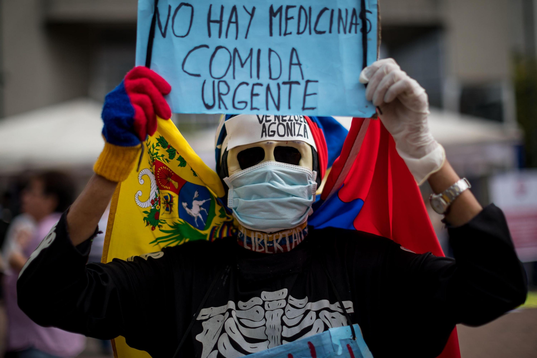 Una persona despliega un cartel durante una protesta por la escasez de medicinas y tratamientos para la salud en Caracas. (Foto: EFE)