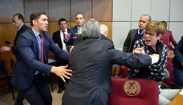 El senador Enrique Riera, del Partido Colorado, es sujetado luego de agredir al legislador Paraguayo Cubas, de Cruzada Nacional, después de un cruce de acusaciones verbales durante una sesión en Asunción. (Foto: EFE)