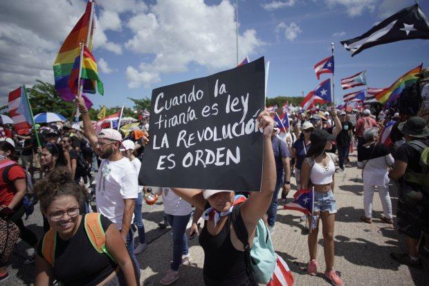 Una mujer sostiene un cartel mientras la gente se dirige a la autopista Las Américas en San Juan, Puerto Rico, en el día 9 de las continuas protestas que exigen la renuncia del gobernador Ricardo Rosselló. (Foto: AFP)