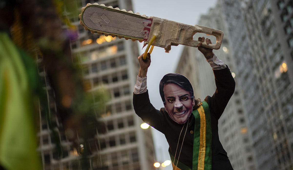 Un activista con una máscara que representa al presidente brasileño Jair Bolsonaro participa en una manifestación contra las políticas ambientales y la destrucción de la selva amazónica en Río de Janeiro. (Foto: AFP)