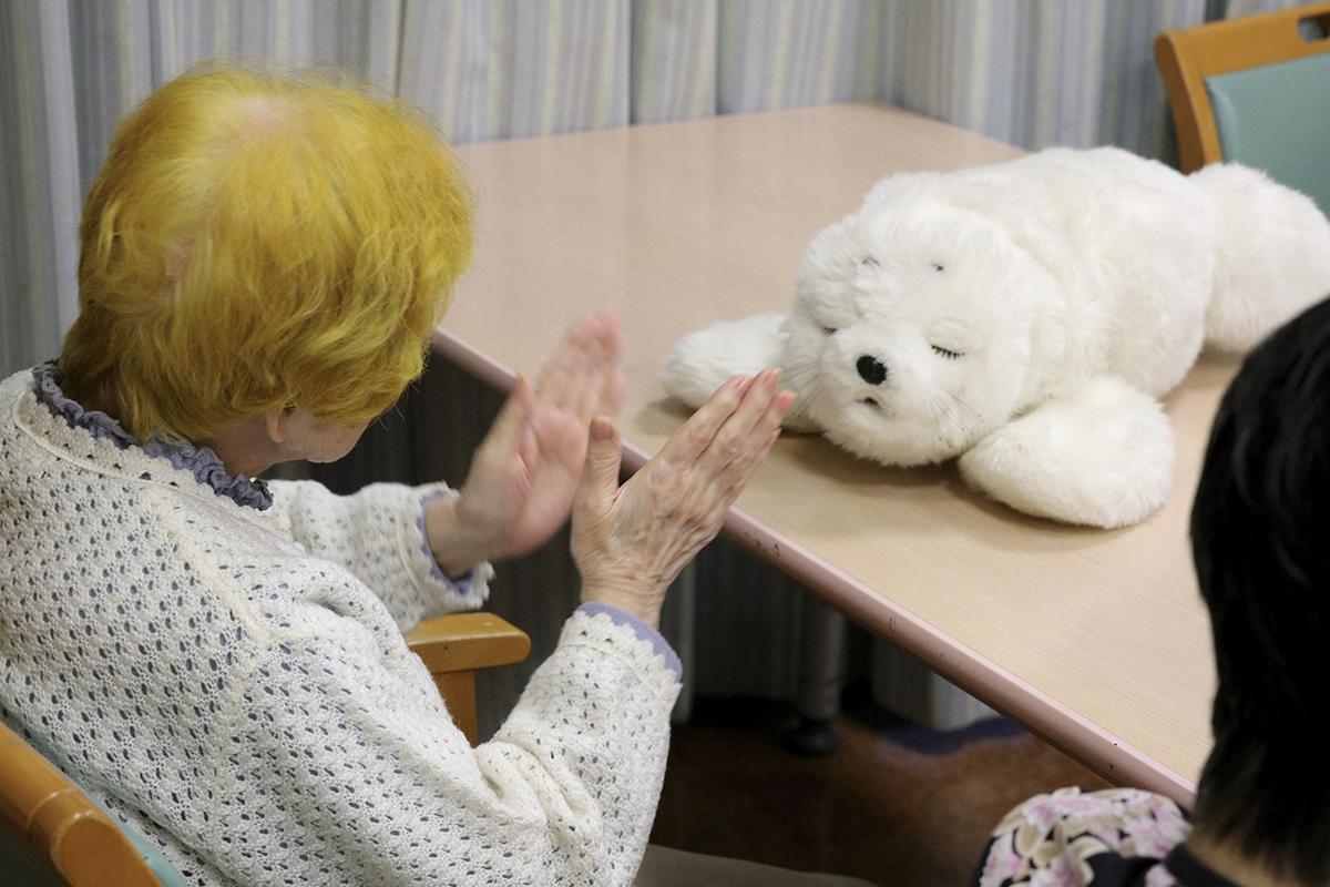 Una anciana interacciona con el robot bebé foca Nuka en una residencia en Japón. (EFE)