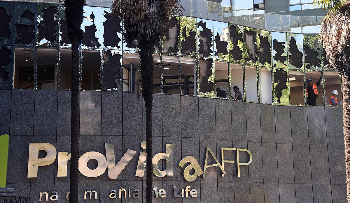 Trabajadores repararon daños causados por manifestantes enojados con el gobierno chileno en un edificio de un fondo de pensiones en el barrio de Providencia de Santiago. (Foto: AFP)