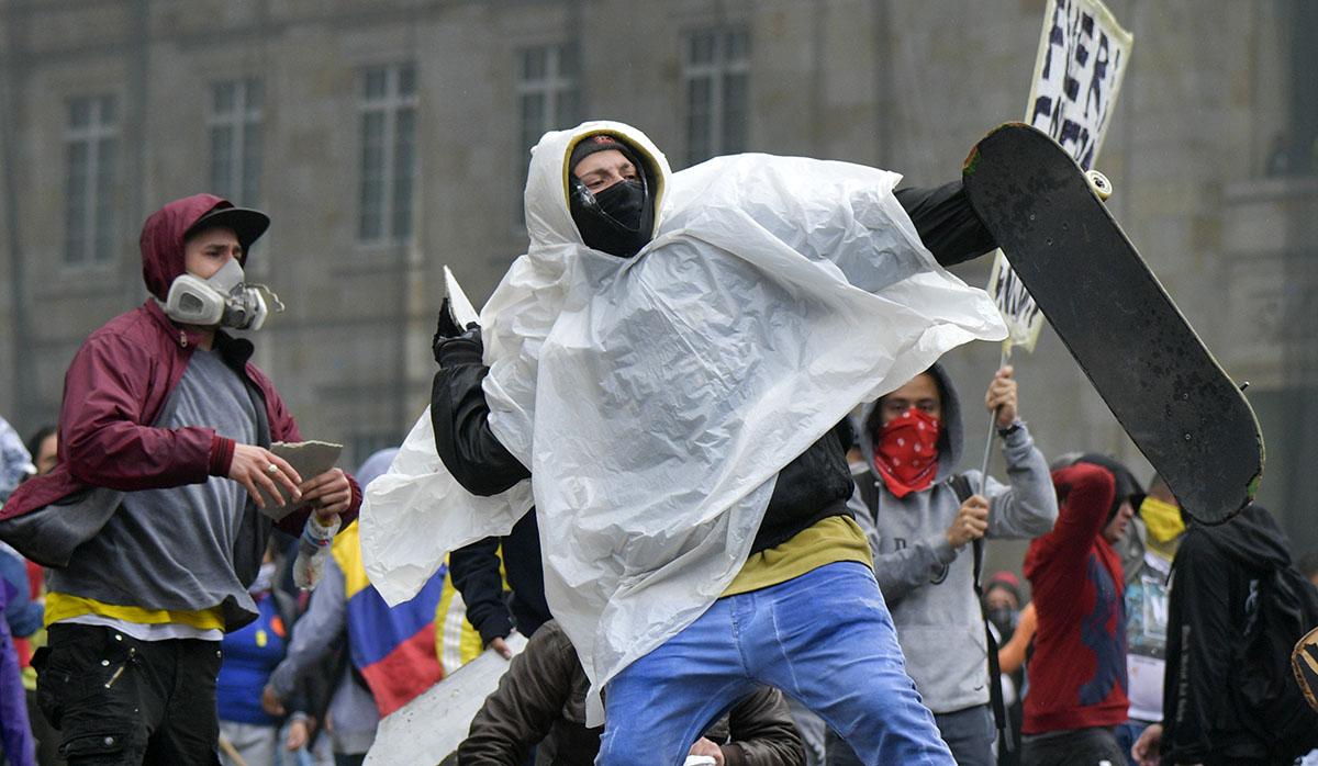 Manifestantes arrojan piedras a policía durante huelga nacional convocada por estudiantes, sindicatos y grupos indígenas contra el gobierno del presidente colombiano Iván Duque, en Bogotá. (Foto: AFP)